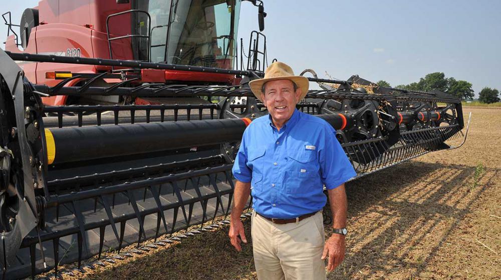 A man standing in a field next to farming equipmen.