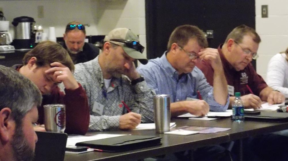 Agents seated at table taking notes during training.