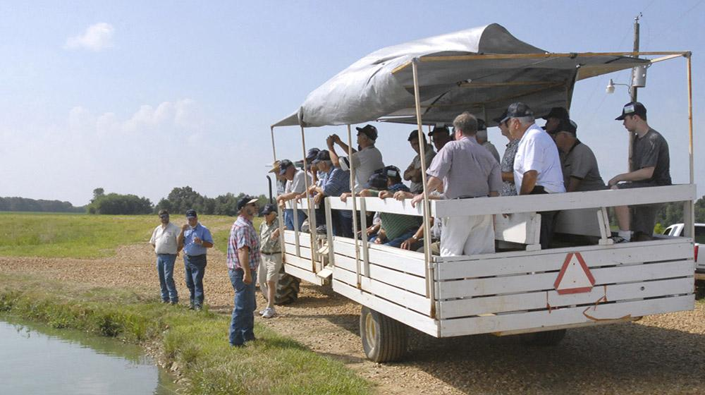 Okolona farmer Jay Schmidt explains his catfish farming techniques to a wagon-load of men from Virginia on July 29, 2010. The group also heard Schmidt explain farming practices related to corn, soybeans and truck crops. The Roanoke-Botetourt (Virginia) Farm Tour brought 40 men to learn about Mississippi agriculture. (Photo by Linda Breazeale)