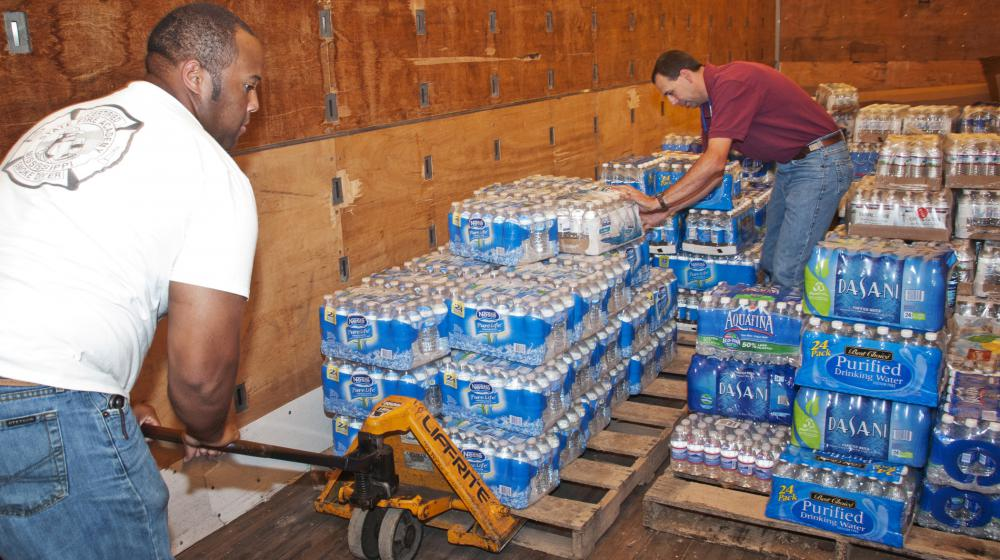 B.J. McClenton, Monroe County Extension director (left), and Charlie Stokes, area Extension agent (right), unload water from a semi-trailer to distribute to tornado victims in Monroe County. MSU Extension Service employees are storing and distributing supplies to those affected by the April 26 and 27 tornadoes. (Photo by Scott Corey)