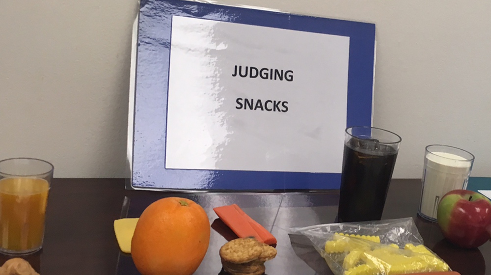 Snacks, to be judged at a 4-H volunteer conference, consisting of an orange, cheese, crackers and carrots, french fries and a hot dog with a glass of soda, and an apple, a glass of milk, and a poptart