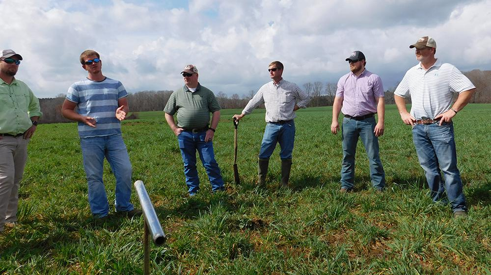 Man talking in grassy field while five other men listen.