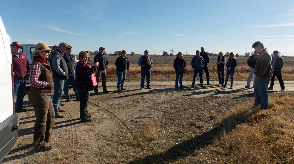 Group of people standing on dirt road on a farm listening to man giving instructions.