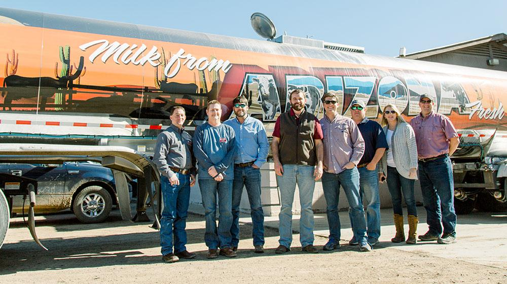 Group of people standing in front of Arizona dairy truck.