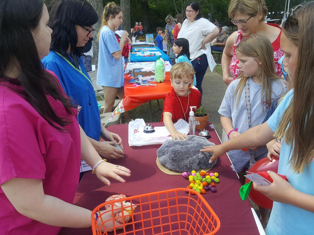 Volunteer teenagers use a prop resembling the human brain to demonstrate brain function to children.
