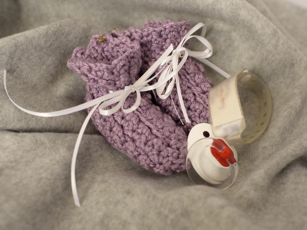 Still life arrangement of a pair of knitted infants booties, a hospital ID band and a pacifier.