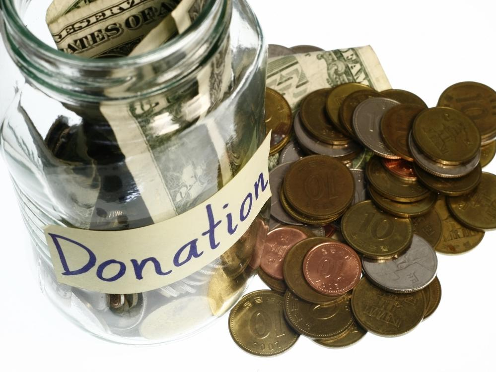 A glass donation jar filled with dollar bills and coins has more money scattered beside it.