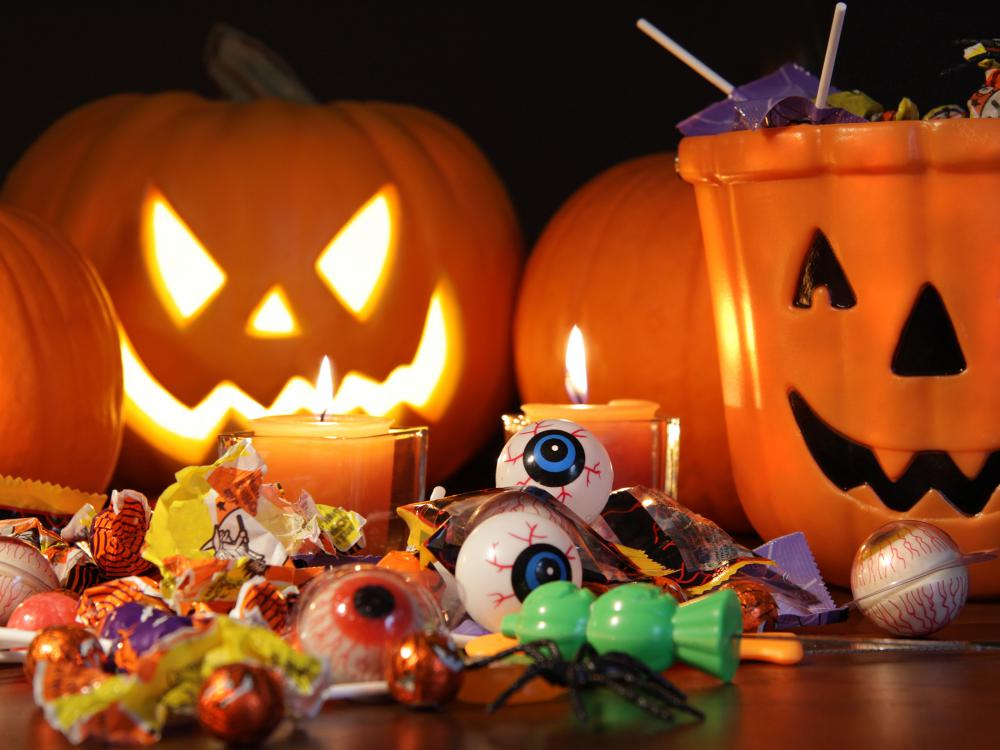 Orange pumpkins and a carved jack-o-lantern sit on a table behind a smiling ceramic jack-o-lantern candy dish. Toys, candy and candles are displayed in front of the pumpkins.