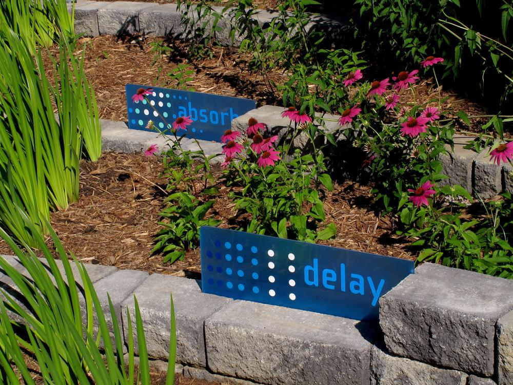 """Blue signs stating """"absorb"""" and """"delay"""" mark brick tiers in a landscape growing pink flowers and reed-like stems."""