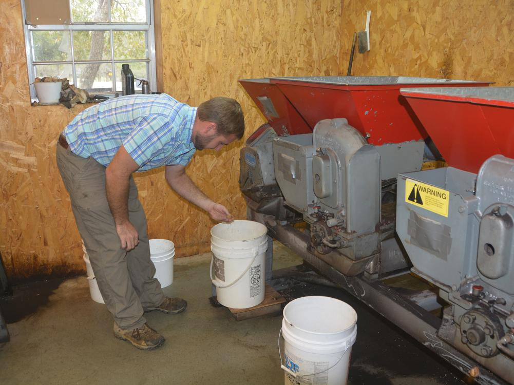 Man leans over a 5-gallon bucket placed under a large mechanical unit inside a building.