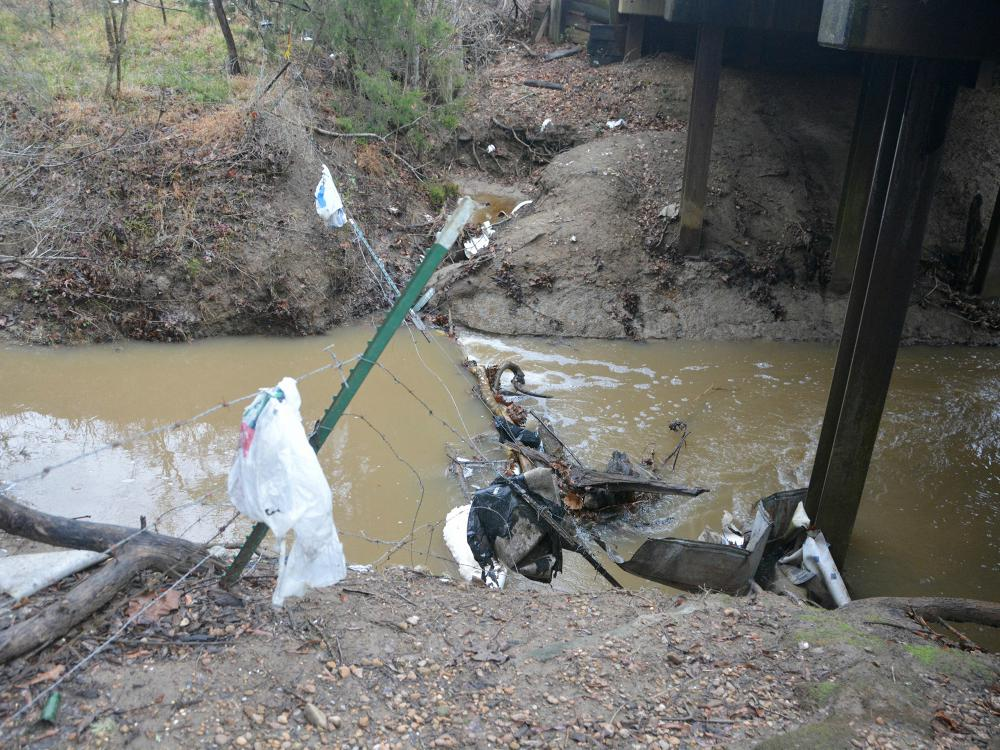 A drainage ditch with moving water, limbs, and trash.