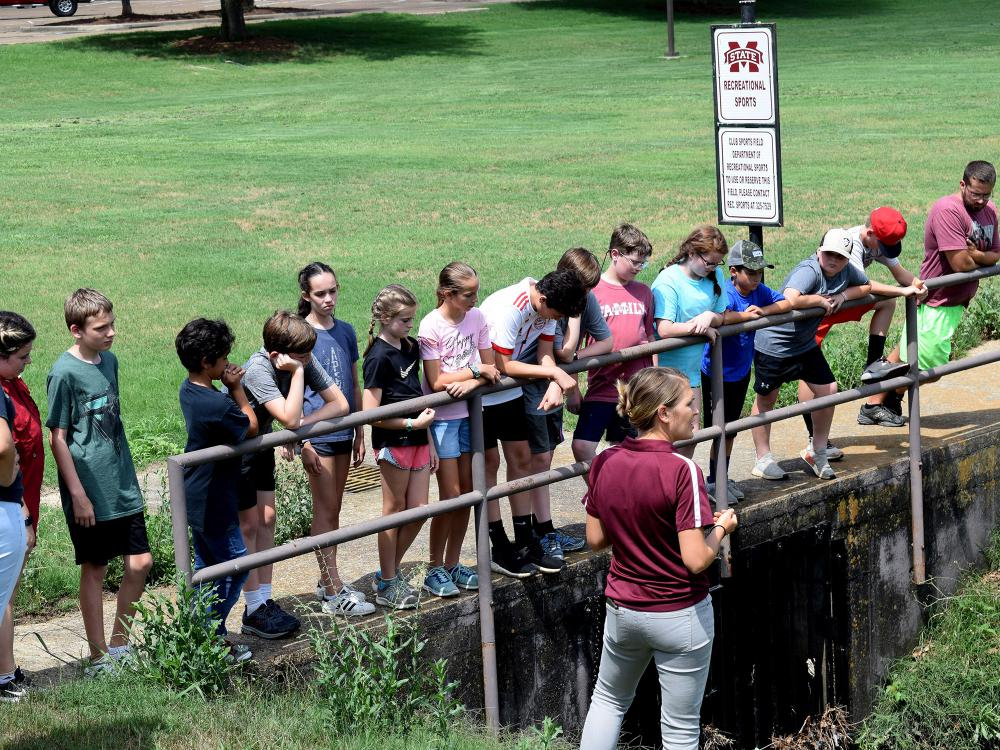 More than a dozen young people listen to a teacher while they stand on a cement bridge overlooking a large ditch.