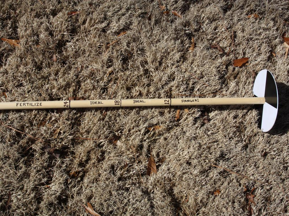 A wooden pole with hash marks at 12, 18 and 24 inches from a round disk with alternating black and white quadrants rests on brown grass. Danger is written below the 12-inch hash, ideal is written in the middle section, and fertilize is written above the 24-inch hash.