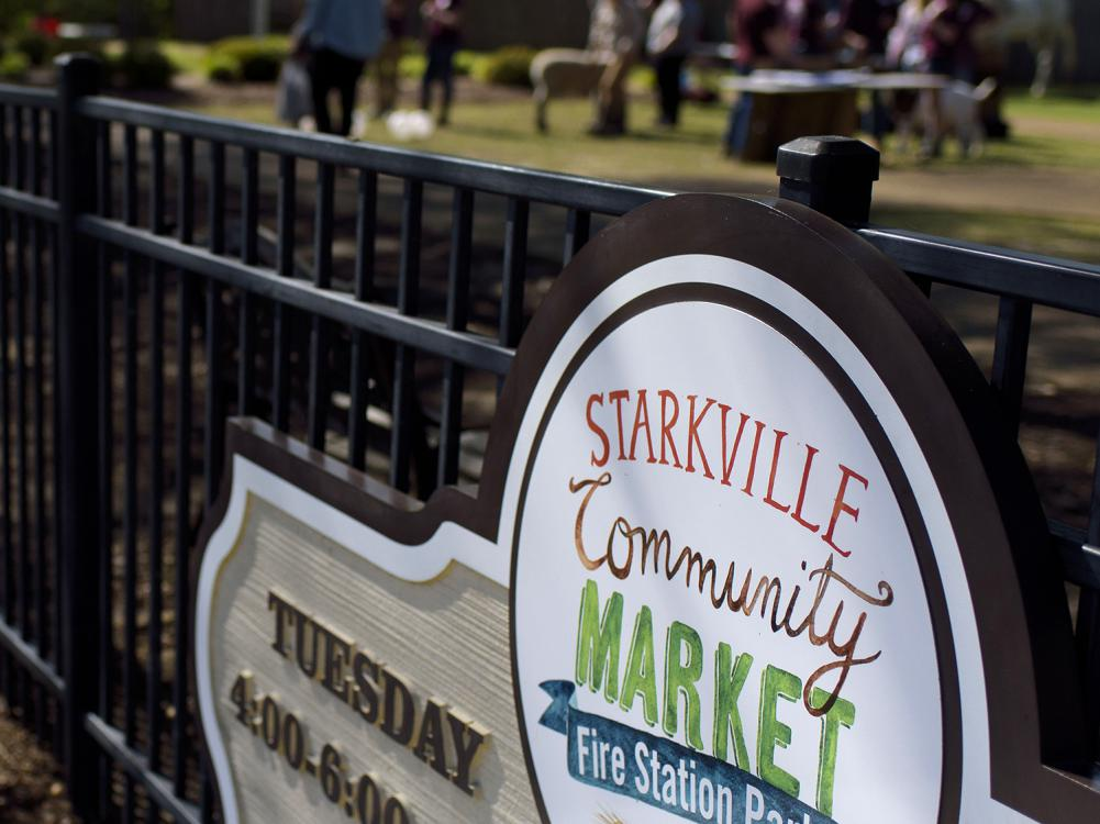 Shoppers can be seen browsing in the background of a farmers market sign.