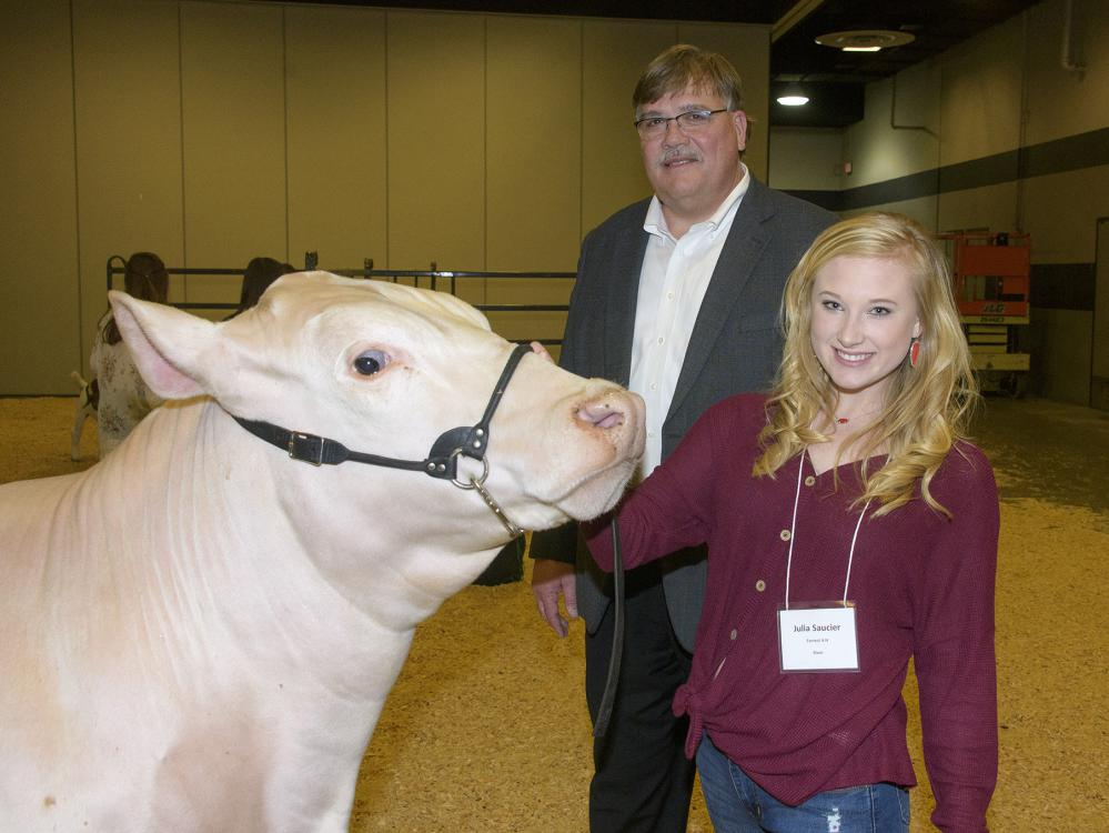 A teenage girl holds the halter on the face of her muscular, white steer as she and a tall man standing behind them look at the photographer.