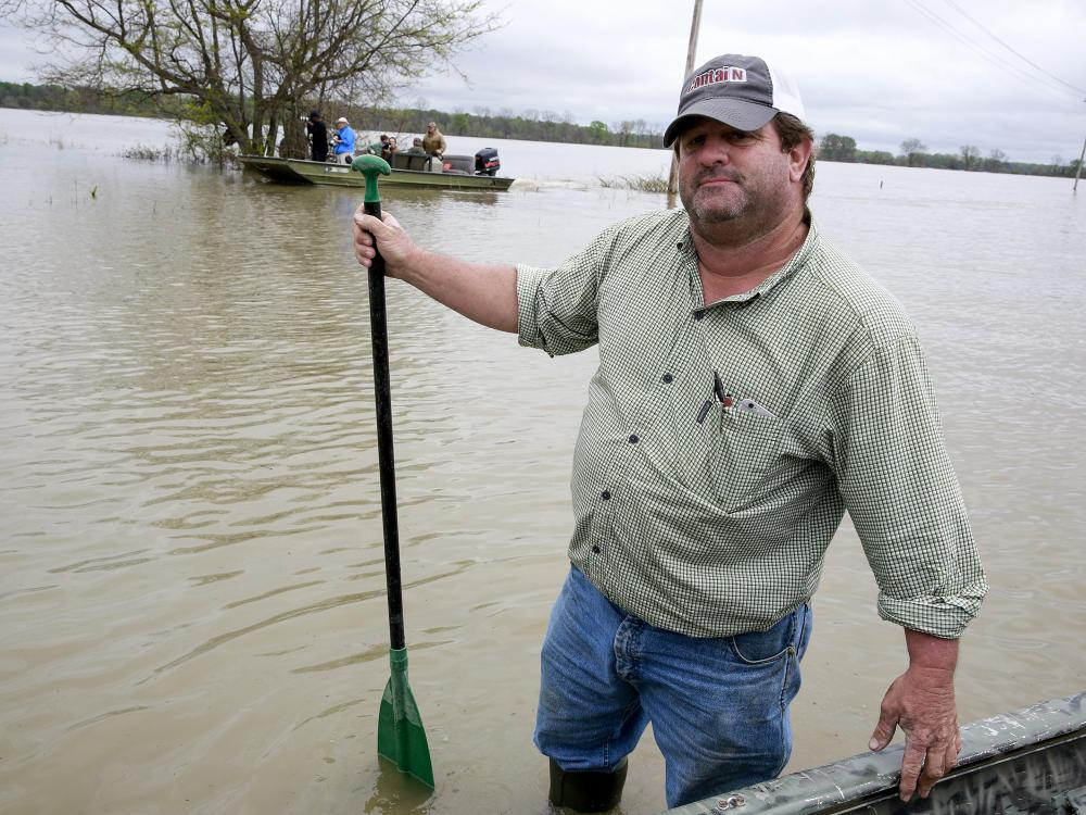 A man in work clothes, baseball cap and wading boots stands in water outside his boat holding a paddle.