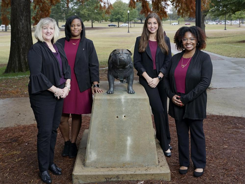 Four women stand around the Bully statue on the Mississippi State University campus.