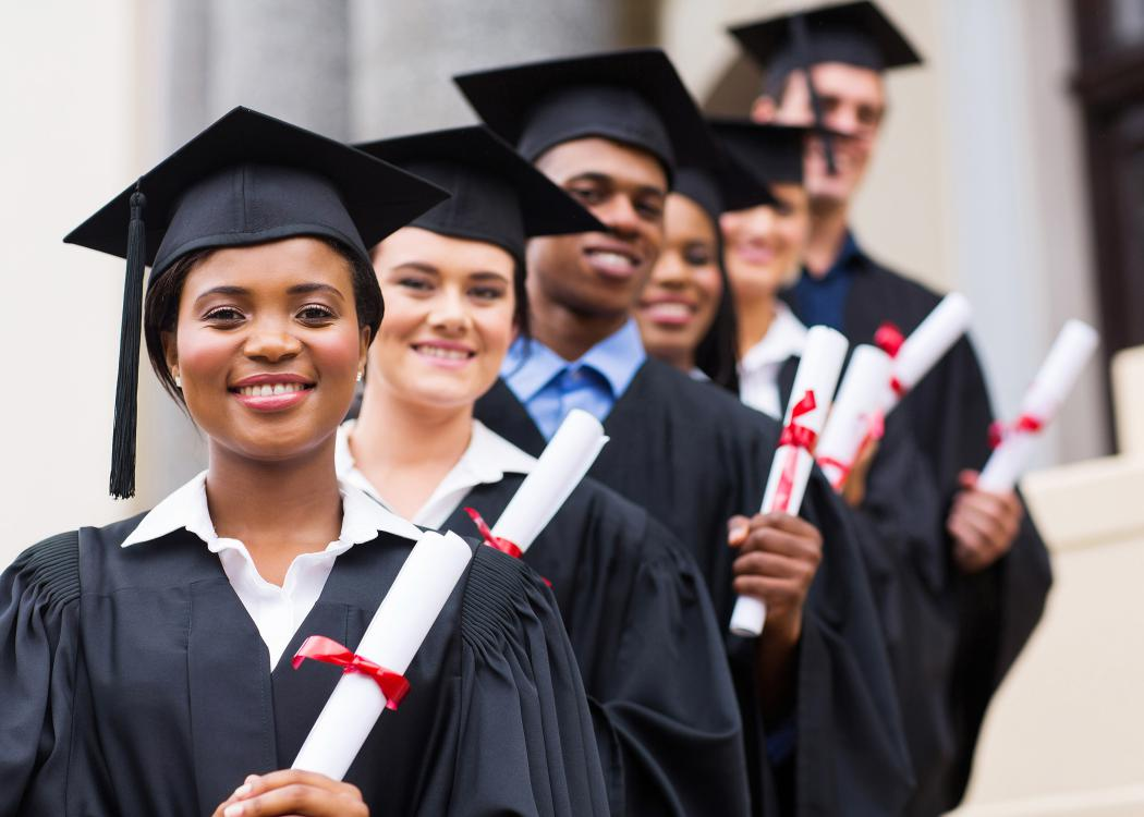 A group of smiling graduates pose in caps and gowns.