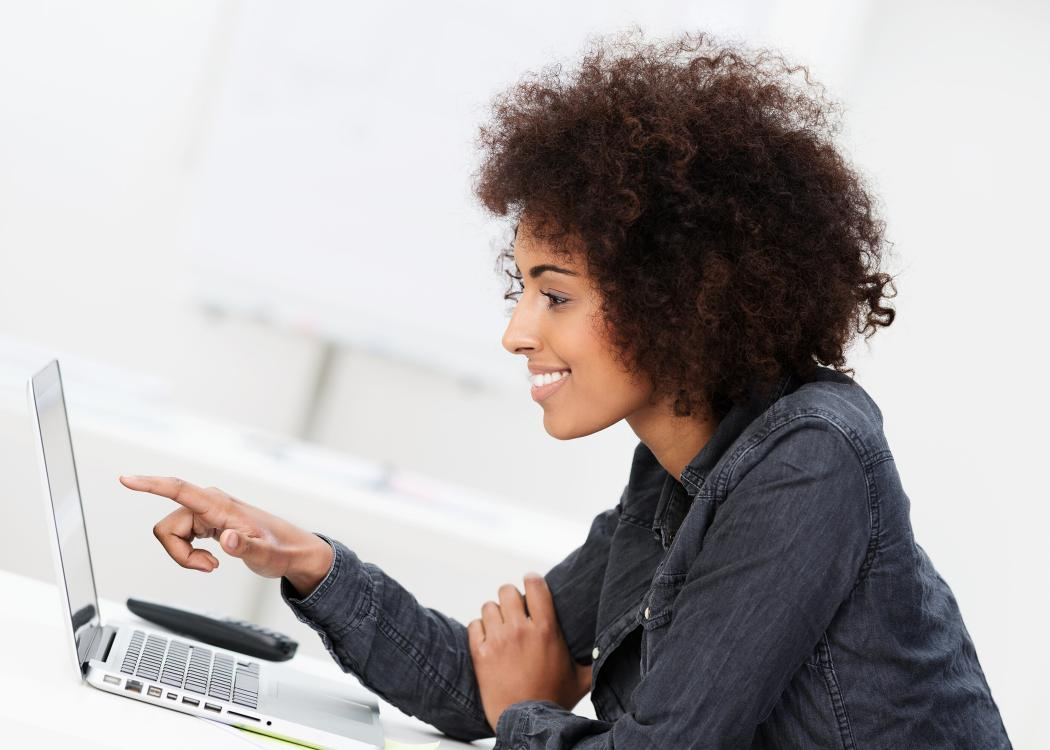 Woman points at computer screen.