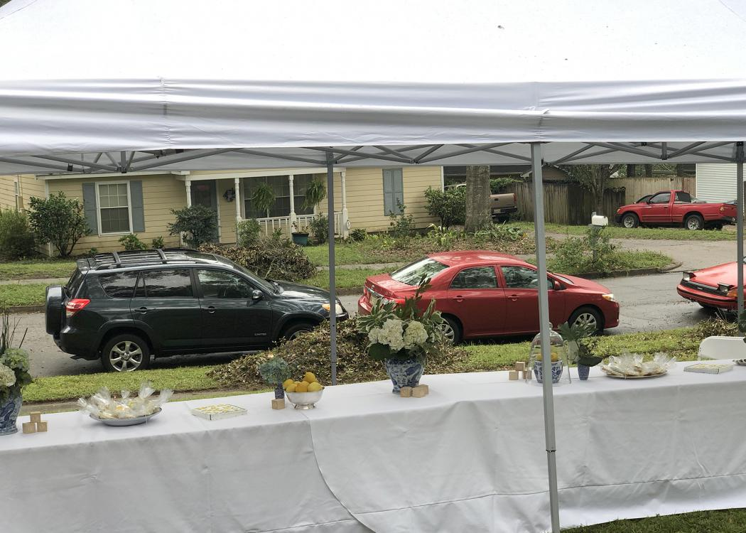 From inside a tent, cars can be seen lined up on the street.