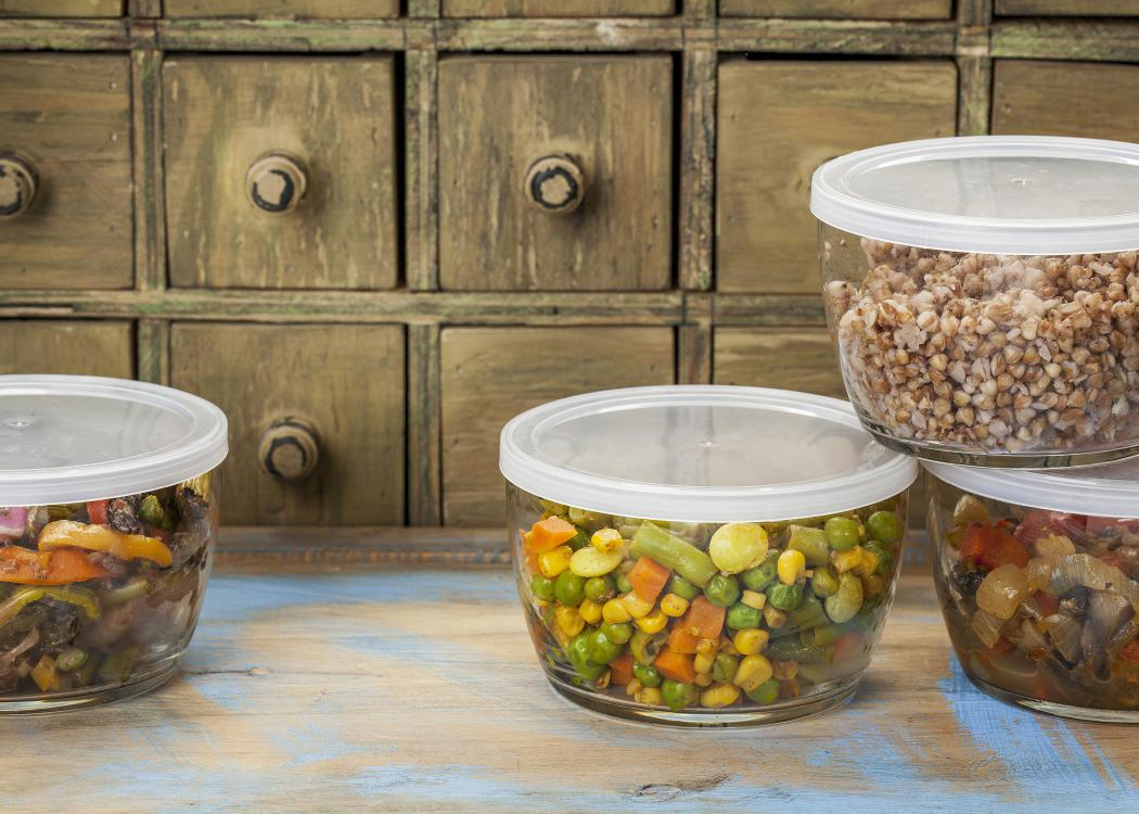 Four glass containers with plastic lids contain food leftovers.