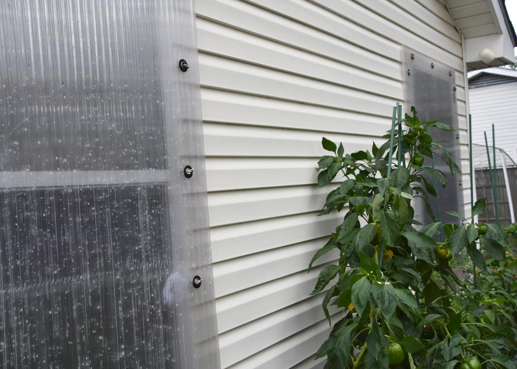 A clear panel covers a window on the exterior of a house.