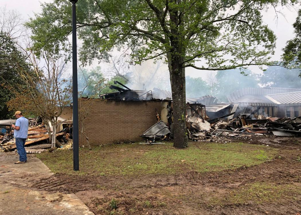 Smoke rises from a mostly burned structure.