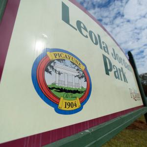 "A white sign lists ""Leola Jordan Park"" in green lettering."