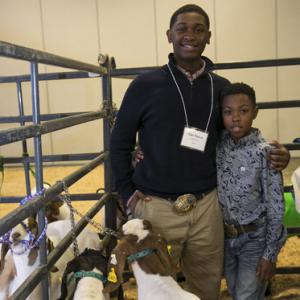 A teenage boy stands next to a young boy while a brown and white goat stands in front of them.
