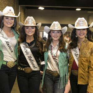 Four teenage girls wearing white cowgirl hats and white sashes stand smiling at the camera.