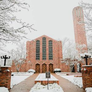 Wide view of a large brick building with three doors and three tall stained glass windows and a brick bell tower to the right.