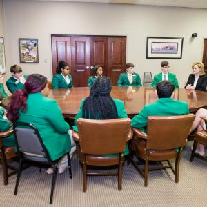 Fourteen teens in green jackets sit around a round table, and they focus on a female speaker, also sitting at the table, dressed in black jacket and white polo.