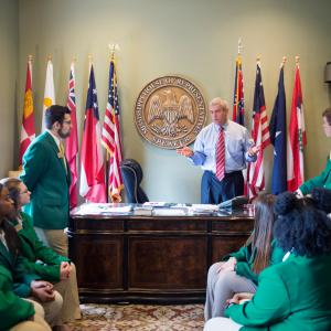 A man in a blue polo shirt and red tie, flanked by the State Seal of Mississippi and national flags, stands behind a desk and talks to seven teens, each wearing green sport jackets.