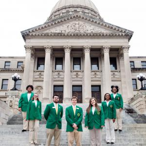 Seven teenagers wearing green blazers and tan slacks form a U standing on steps in front of six gray columns.