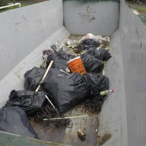 Full black trash bags gathered in a large metal container.