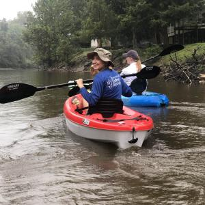A smiling woman paddling a red kayak looks back at the camera.