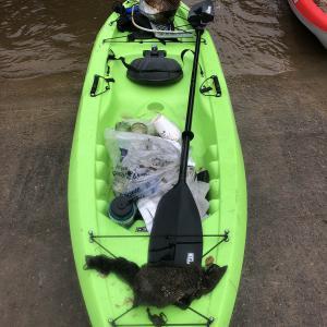 Bright green kayak holding trash at the edge of water.