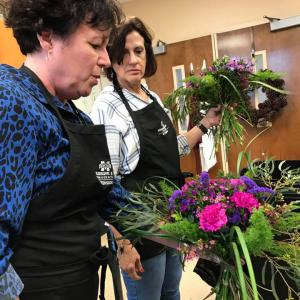 Two women viewing floral bouquets they have made.