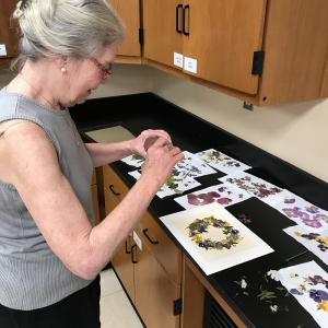 A woman creating a pressed floral picture.