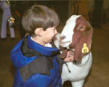 Ten-year-old Nolan Webb of Lafayette County 4-H has one last visit with Showboy, the grand champion market goat at the 2002 Dixie National Junior Livestock Show in Jackson, Miss., on Feb. 7, 2002.