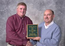 Mississippi State University Extension Service soybean specialist Alan Blaine, left, was presented with the Mississippi Society of        Agronomy's Agronomist of the Year award by the organization's president David Roberts.