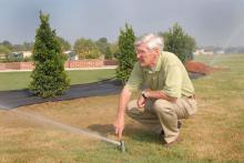 Dr. Wayne Wells adjusts a pop-up irrigation head for best coverage at the R. Rodney Foil Plant Science Research Center at Mississippi State University's North Farm. (Photo by Marco Nicovich)