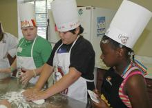 """From left, Lamar Land, Ben Barker and Murritta Lane work as a team kneading dough to make bread. """"Fun with Food"""" participants made many nutritious meals during their week at camp. (Photo by MSU Office of Ag Communications)"""