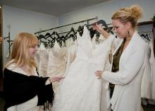 Jennifer Burt, left, and Christine Barker, of Christine's Couture in Starkville, examine the intricate patterns of beading and lace that commonly adorn authentic designer wedding gowns. Handsewn embellishments like these are never seen on counterfeit dresses. (Photo by Scott Corey)