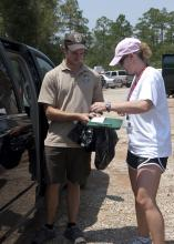 Vivian Cade with Mississippi State University Extension Service signs the paperwork to receive a bird to transport to the Wildlife Rehabilitation Center in Gulfport. (Photo MSU Extension/Alicia Barnes)