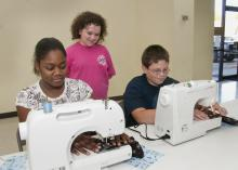 """Calhoun County youth have an opportunity to learn the art of sewing through a new 4-H club named """"A Stitch in Time."""" Operating the new computerized sewing machines donated by Singer Co. and """"Heirlooms Forever"""" of Tupelo are, from left, Keyonia McGuirt of Pittsboro and Taylor Liles of Calhoun City. Observing is Hannah Long of Calhoun City. (Photo by Scott Corey)"""