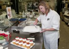 Lorrie Bryan, cake decorator at the Mississippi State University Fountain Bakery, creates Bully's pawprints to cupcakes after whipping up a batch of maroon frosting. (Photo by Scott Corey)