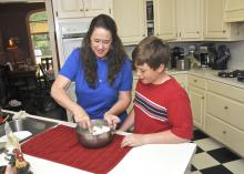 Debbie Huff and her youngest son, John Mark, prepare goat cheese in their kitchen. The Huffs' four sons show dairy goats in 4-H and also make and sell goats' milk products.