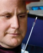 Dr. Todd Archer examines a tracheal stent and accompanying stylet, which allows passage of the stent into the proper location in the dog's windpipe. (Photo by MSU College of Veterinary Medicine/Tom Thompson)
