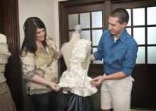 Mississippi State University senior Justin Phelps of Madison shows alumna Robin Cox the draping project he completed in the apparel, textiles and merchandising program. Cox returned to her alma mater to share her career experiences as a corporate merchandise planner for national retailer jcpenney during the Senior Showcase. (Photo by MSU Ag Communications/Scott Corey)